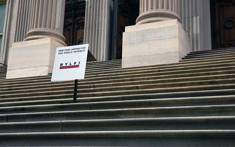 Image shows a NYLPI sign on the steps of New York's Tweed Courthouse in Lower Manhattan
