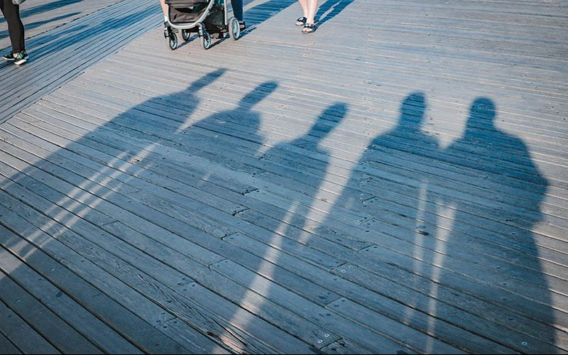 A family is silhouetted on a boardwalk