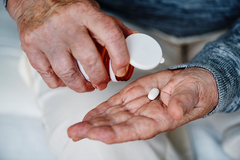 A senior dispenses a pill from a bottle into their hand