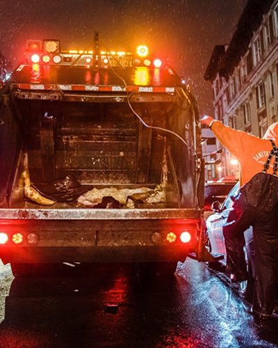 A photo shows a Sanitation Salvage truck driving through New York in the middle of the night