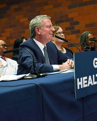 "Image shows Mayor de Blasio announcing ""Guaranteed Health Care for All"""