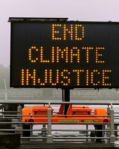"Image shows a sign saying ""end climate injustice"""